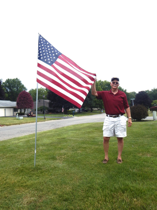 Ken Abell of Howland Rotary Club places an American flag in a yard in Howland as part of a new fundraiser by the Rotary. Photo: Tribune Chronicle / Bob Coupland