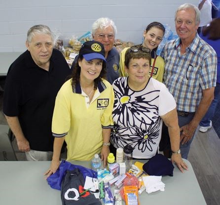 Rotary Club of Niagara Falls president June Mergl, left, and Niagara Falls Community Outreach fundraising co-ordinator Chris Watling show of the contents of one of the summer survival pack that the soup kitchen will distribute to clients. Joining Mergl and Watling in back are, from left, Rotarians Ron Lyons, Jim Craig, Emily Barry and John Corfield. Photo: Richard Hutton/Metroland