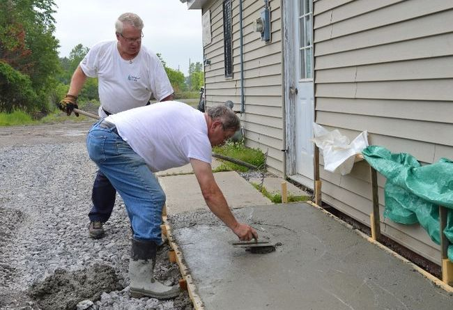 Stirling Rotarian Bill Vaughan smoothes a section of freshly poured concrete that has become the extended loading pad at the Stirling Community Cupboard (Food Bank) as Rotarian Doug Roberts stands by, ready to lend a hand. The larger pad and rebuilt driveway were part of a recent project undertaken and financed by the local Rotary club. Photo: Terry Vollum