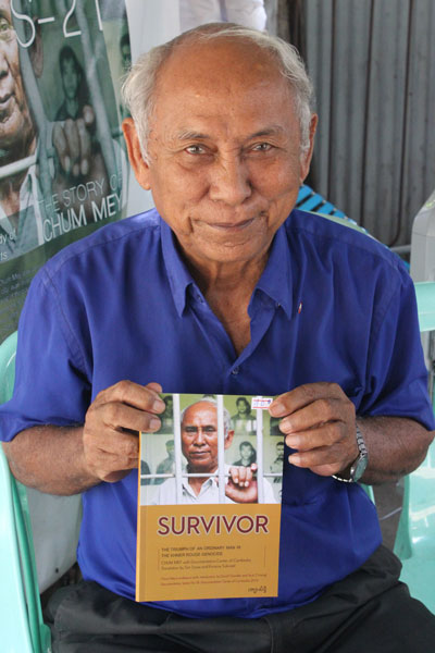 Chum Mey, one of the few survivors of the Khmer Rouge imprisonment, with his book 'Survivor', where he narrates his experiences in the Tuol Sleng prison.