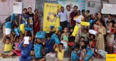 Toybank volunteers helping children play board games.