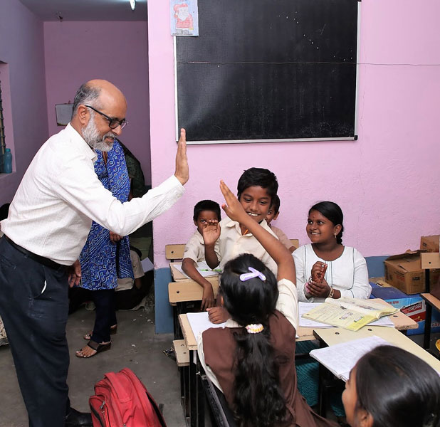 The then President of RC Bangalore Ranga Rao gives a hi-five to a student in a Happy School.