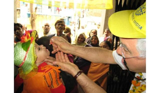Dunwoody Rotarian Roy Wise giving polio vaccine drops to a child in India.