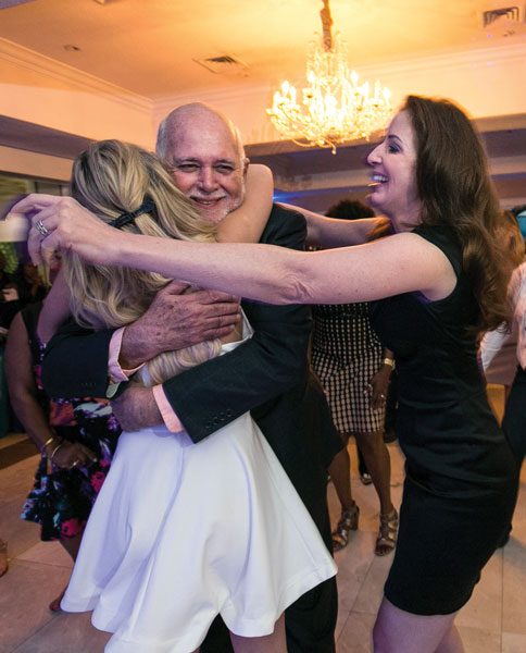 Rassin embraces his daughter Michele (right) and granddaughter Bella at a party thrown by Bahamian Rotarians in honour of him and Esther.