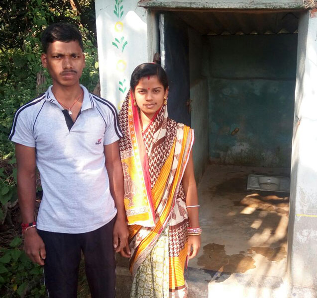 Bhajanandini Biswas with her ­husband in front of their new toilet.