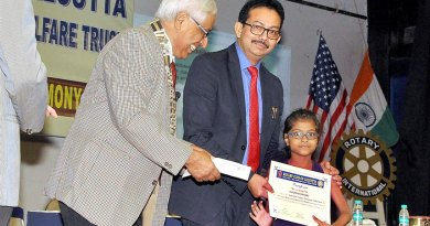 RC Calcutta President Saumen Ray and Satyam Roychowdhury, MD, Techno India Group, present an award to a child.
