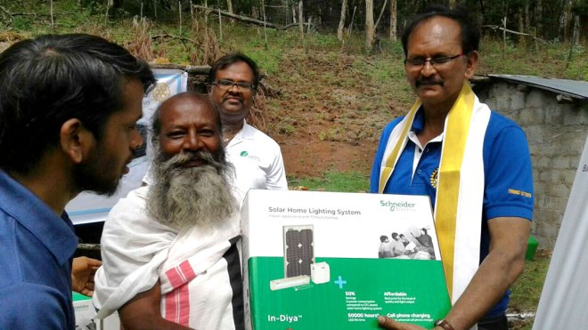 Club President Raghu Allam (right) gives a solar lighting system to a villager.