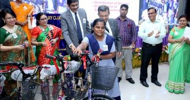 RIDE Bharat Pandya and PDG Sam Patibandla handover a bicycle to a student in the presence of Club President TS Sashikala and other Rotarians.