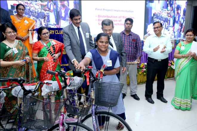 RIDE Bharat Pandya and PDG Sam Patibandla handover a bicycle to a student in the presence of Club President T S Sashikala and other Rotarians.