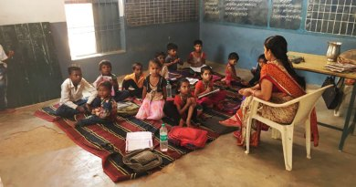 Children seated on the floor in one of the schools in Sirol, before RC Gwalior Imperial intervened with a makeover that included benches and desks for the students (facing page).