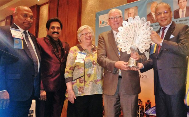 PRIP K R Ravindran honours RI President Ian Riseley and Juliet in the presence of RID C Basker and Event Secretary John Daniel.