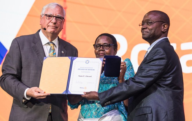 RI President Ian Riseley presents Norah Owori and son with a posthumous RI Award of Honour for Sam F Owori.