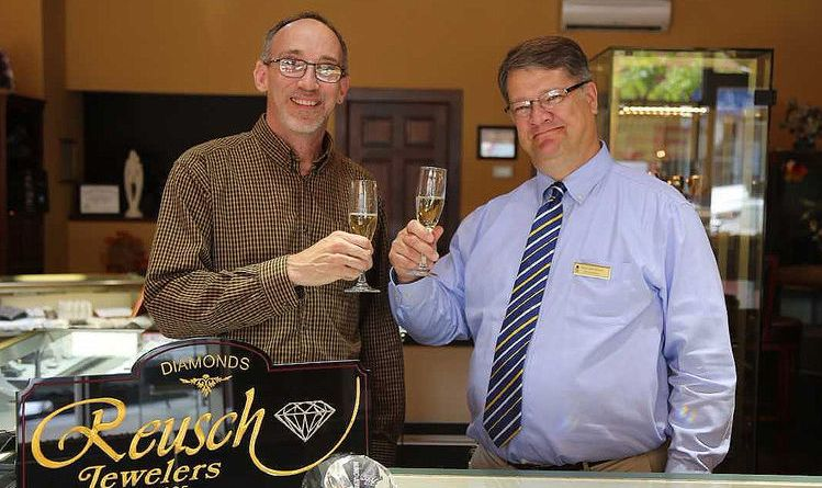 Rotary Club of Petoskey's Diamonds and Denim Chair Rtn Reg Smith (left) with Reusch Jewelers staff member Mike Hempstead toast to the chance for someone to win the diamond valued at $6,000, by purchasing a glass of champagne at the fifth annual Rotary Diamonds & Denim gala. Photo: Reusch Jewelers