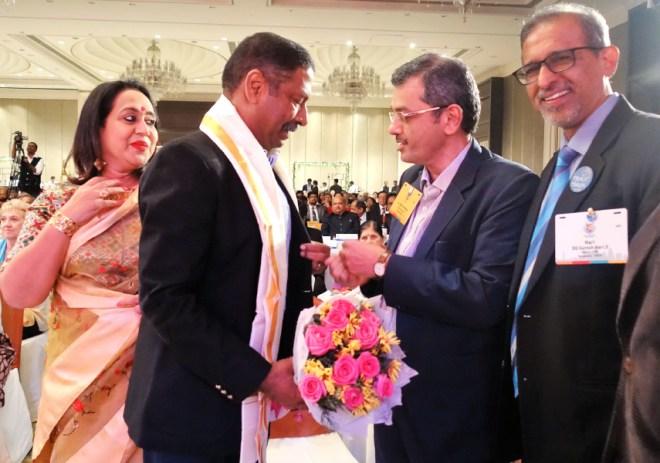 RIDE Bharat Pandya puts a Gandhi pin on Rtn Ravi Shankar, as Paola and D 3190 DG Suresh Hari look on.