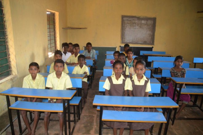 Schoolchildren enjoy better seating through a Rotary project in India.