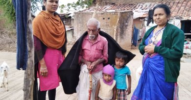 An elderly beneficiary with a woollen blanket given by the club.