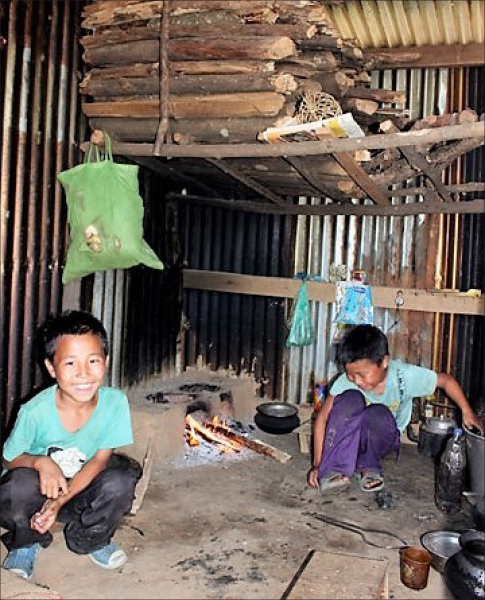 The self-help kids cooking their own food in a portion of a hut.