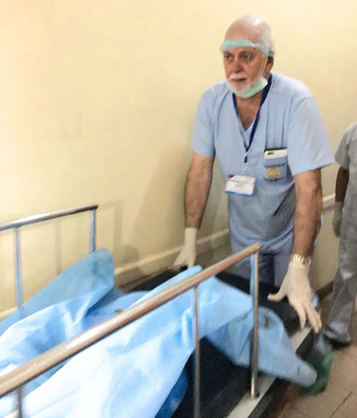 RI President Barry Rassin pushing a stretcher at the medical camp.