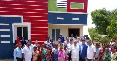 PDG Abirami Ramanathan with Rtn Vinod Sarogi, Project Secretary P B Ravi Kumar and villagers in front of the model house at Kuyil Kuppam village.
