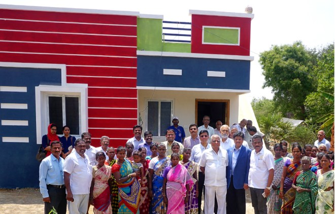 PDG Abirami Ramanathan with Rtn Vinod Sarogi, Project Secretary P B Ravi Kumar and villagers in front of the model house at Kuyil Kuppam village.