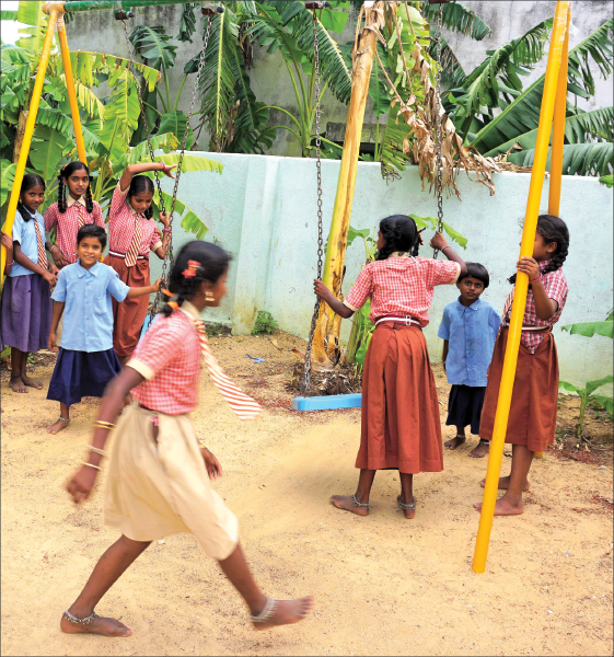 Children using the new play equipment at the government school in Yaluvahalli village, Kolar.