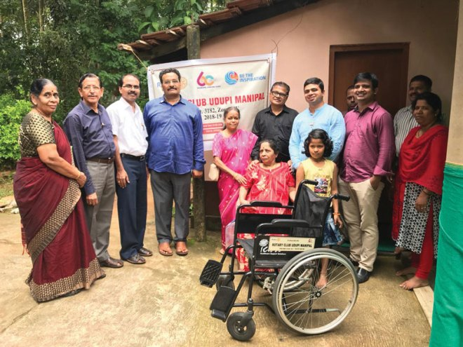 IPP Amit Aravind, along with members of RC Udupi Manipal, provides wheelchair to a physically-challenged woman as part of the club's diamond jubilee projects.
