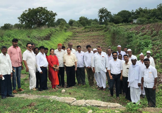 PDG Rajiv Pradhan (seventh from L), and to his right: PDG Deepak and Sucheta Pophale, and RC Omerga's PP Sanjay Aswale with Rotarians and farmers at a desilted stream.