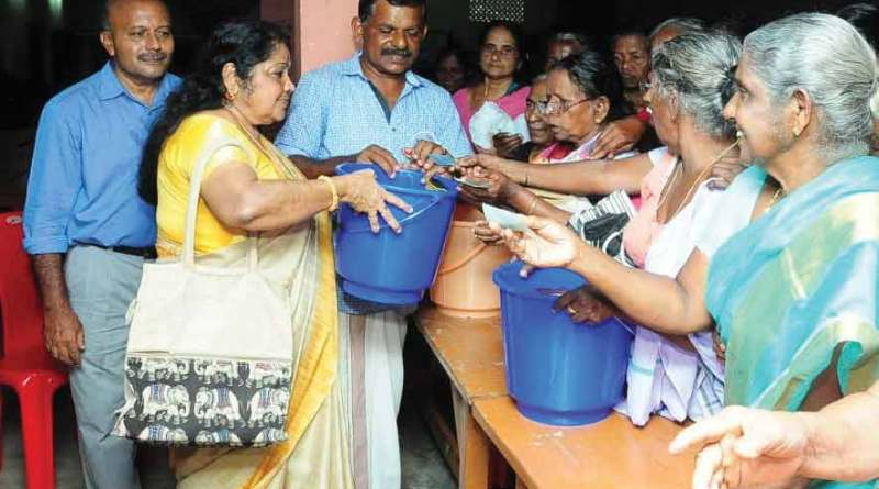 Project Coordinator Vijayalakshmi Nair, along with members of RC Alleppey, distributes household articles to flood victims in Kayalpuram.
