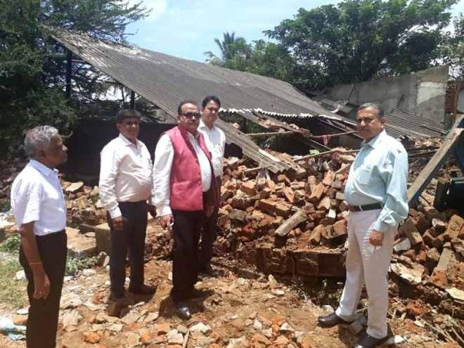 DG Girish Masurkar and PDG Ganesh Bhat survey a flood-hit home, along with few Rotarians.
