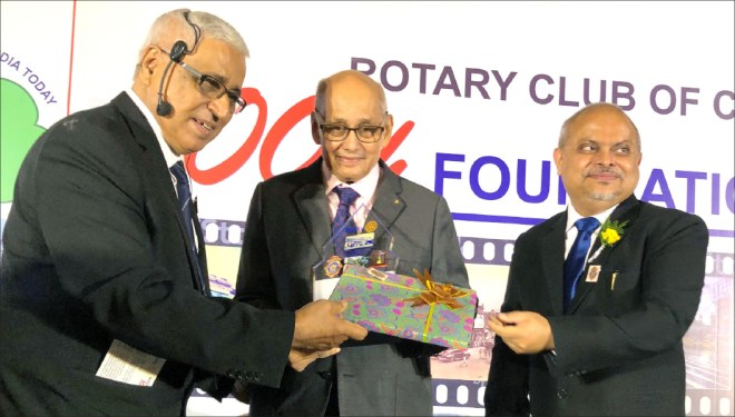Club President Purnendhu Roy Choudhury and Soumen Ray presenting the club bulletin, The Chaka, to PRIP Kalyan Banerjee.