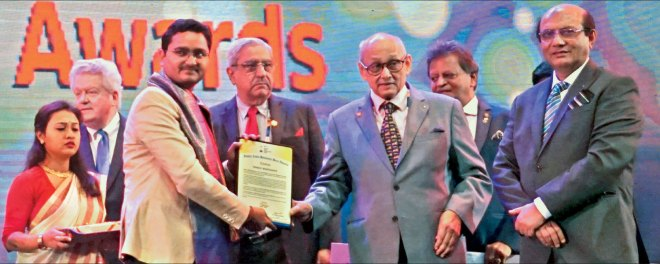 PRIP Kalyan Banerjee honours Bhrigu Borthakur with an award in the presence of RID Kamal Sanghvi, PDG Subhash Jain and RI President Mark Maloney (L).