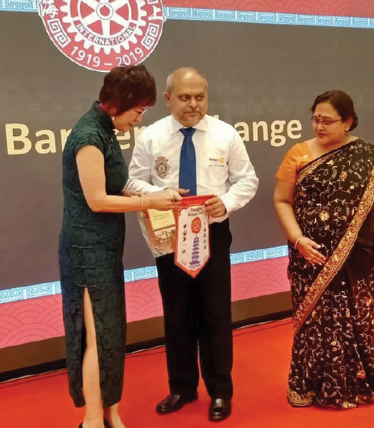 Club President Chowdhury exchanging flags with President of RC Shanghai at Shanghai on their 100th anniversary celebration.
