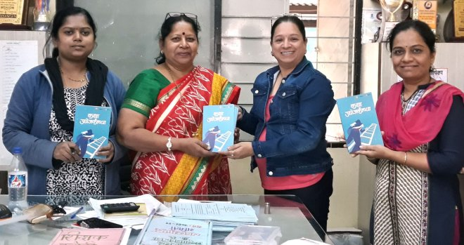 Geetanjali Purohit (second from R) handing over books to a school principal and teachers.