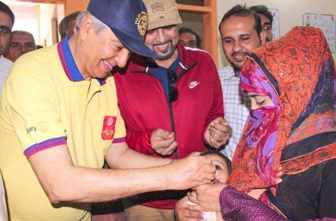 TRF Trustee Aziz Memon administering polio drops to a child.