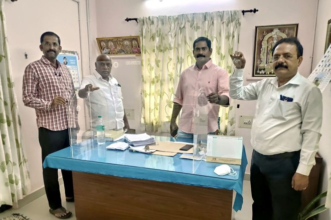 An acrylic Covid shield being installed at a police station by RC Coimbatore Vadavalli members.