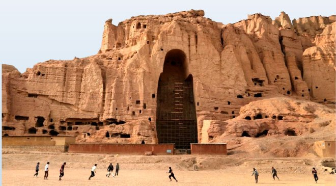 Afghan youth playing in front of the ruined Bamiyan Valley.