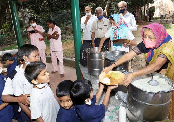 Volunteers Thara and Chandrakala from the Sri Sai Spiritual Centre serve food to the children.
