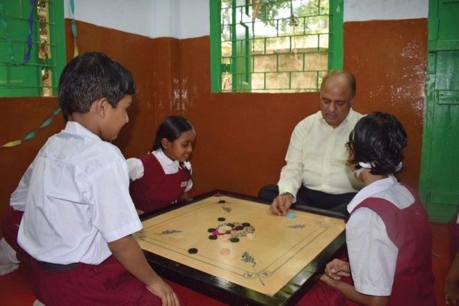 Playing carrom with students at the Paresh Nath Vidyalaya school in Kolkata.