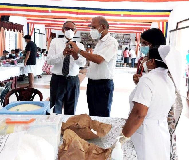 PRIP KR Ravindran and RC Colombo president Nithi Murugesu examining a Covishield vial.