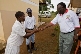 Muyenga Rotarians Japheth Semogerere (right) and Dr. Francis Mukasa (left) greet a young women waiting for treatment.
