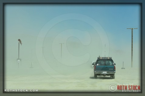 A dust storm blows in while racers scurry to depart at the end of the first day of racing at at SCTA - Southern California Timing Association's Land Speed Races at El Mirage Dry Lake