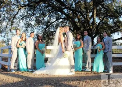 Outdoor wedding party look on as couple kiss under the trees