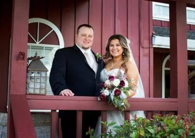 Bride and groom pose for photo in outdoor barn setting, a lovely wedding venue