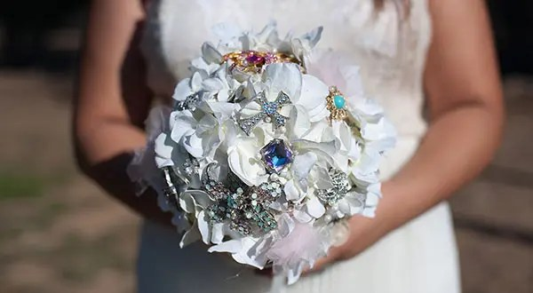 A bride holding her bejeweled wedding bouquet