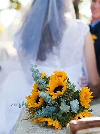 Bride and groom in the background, bouquet of sunflowers in the foreground