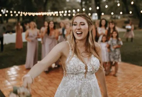Bride tossing her wedding bouquet to the unmarried wedding guests