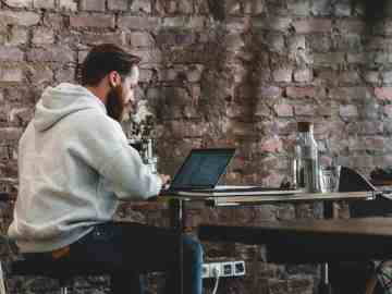 man sitting at a cafe working on his laptop