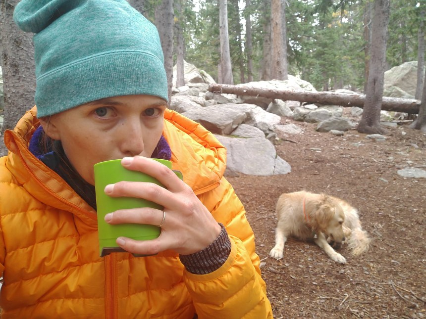 The author is sipping hot coffee on a hiking and backpacking trip. Her dog is in the background.