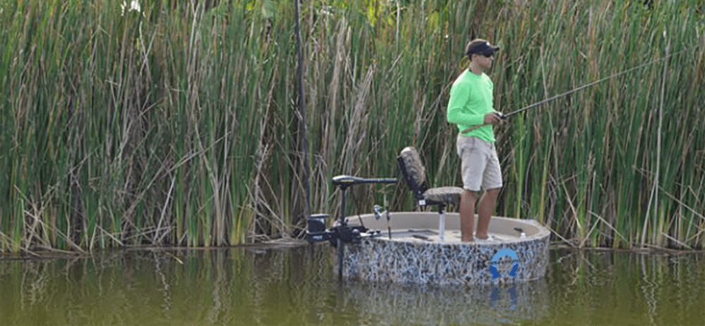 Fisherman standing on he woodsman hunting boat in front of tall grass looking for fish