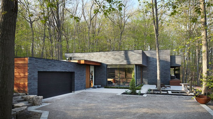 Contemporary home in the forest featuring dark brick exterior 1